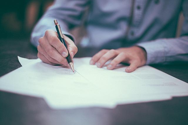 Mann sitzt am Schreibtisch und unterschreibt Vertragsdokumente
