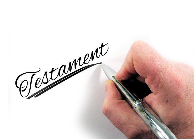 Hand von älterem Menschen mit Stift schreibt das Wort Testament auf ein Blatt